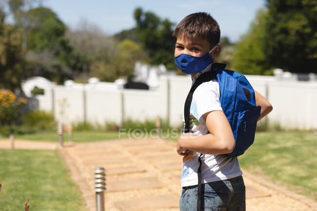 Retrato de menino caucasiano usando máscara facial olhando para a câmera em pé no jardim com mochila no dia ensolarado. proteção e auto-isolamento durante o bloqueio da pandemia do coronavírus covid 19. — Fotografia de Stock