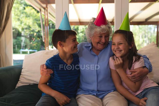 Старша козацька жінка проводить час удома, відзначаючи день народження з онуками, одягаючи капелюхи на вечірки і посміхаючись. Якісний час разом у коронавірусі коїд 19 карантин.. — стокове фото