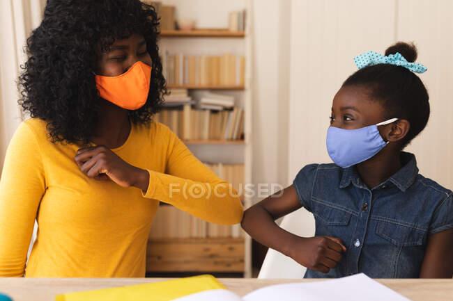Mãe e filha afro-americana usando máscara facial cumprimentando uns aos outros tocando cotovelos em casa. distanciamento social durante o bloqueio de quarentena do coronavírus covid 19. — Fotografia de Stock