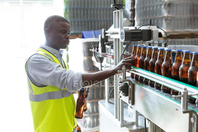 Operaio afroamericano che lavora in una birreria, ispeziona le bottiglie su un nastro trasportatore. Produzione e birrificio. — Foto stock