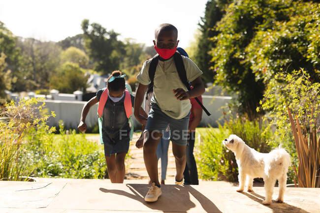 Père, fille et fils afro-américains portant un masque facial grimpant les escaliers sur le jardin par une journée ensoleillée. distanciation sociale pendant le confinement de quarantaine de coronavirus de covidé 19 — Photo de stock