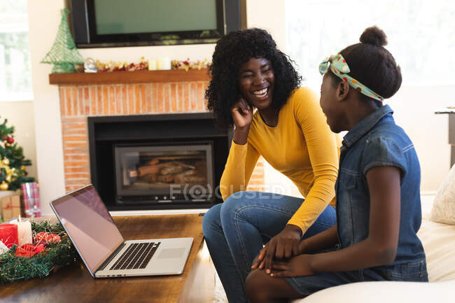 African american mother and daughter smiling while having a video chat on laptop in the living room at home. social distancing during covid 19 coronavirus quarantine lockdown. — Stock Photo