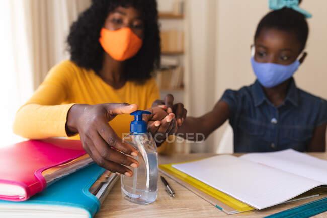 Mãe afro-americana usando máscara facial higienizando as mãos de sua filha usando máscara facial em casa. distanciamento social durante o bloqueio de quarentena do coronavírus covid 19. — Fotografia de Stock