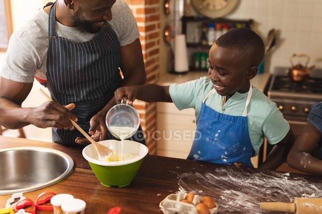 Il padre e il figlio afroamericano indossano grembiuli che cuociono in cucina a casa. Natale festa tradizione celebrazione concetto — Foto stock