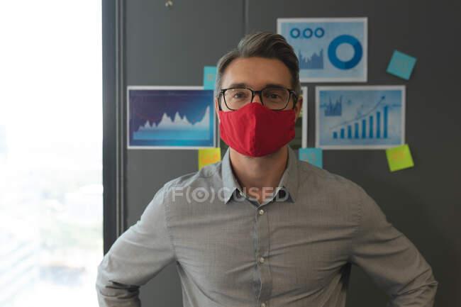 Retrato de homem caucasiano usando máscara facial em pé no escritório moderno. bloqueio de quarentena por distanciamento social durante a pandemia do coronavírus — Fotografia de Stock