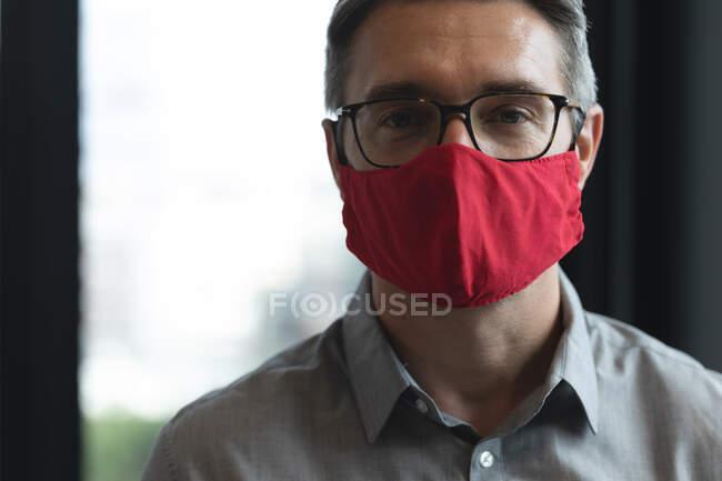 Retrato de homem caucasiano usando máscara facial no escritório moderno. bloqueio de quarentena por distanciamento social durante a pandemia do coronavírus — Fotografia de Stock