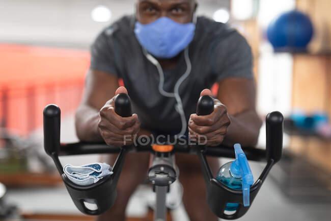 Porträt eines fitten afrikanisch-amerikanischen Mannes mit Gesichtsmaske und Kopfhörern, der auf einem stationären Fahrrad in der Turnhalle trainiert. Soziale Distanzierung von Quarantäne während der Coronavirus-Pandemie — Stockfoto