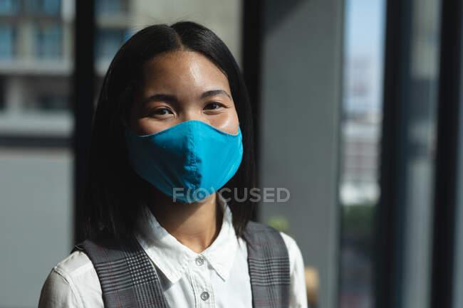 Portrait de femme asiatique portant un masque facial debout dans un bureau moderne. isolement social mise en quarantaine pendant une pandémie de coronavirus — Photo de stock