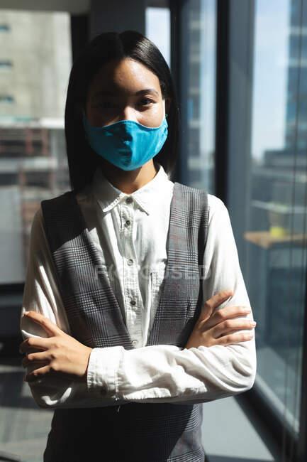 Средняя часть азиатской женщины в маске, стоящей со скрещенными руками в современном офисе. социальная изоляция от карантина во время пандемии коронавируса — стоковое фото