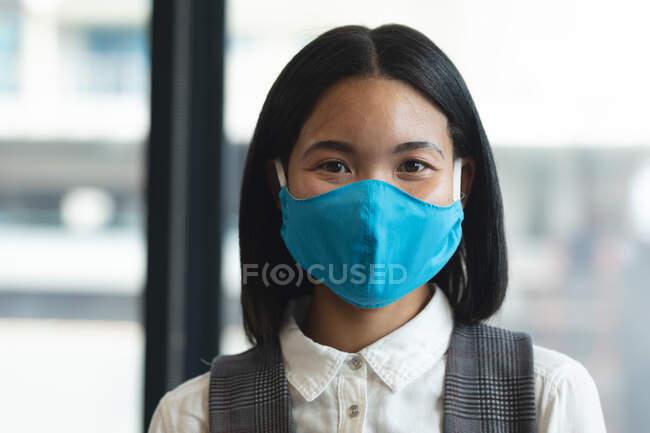 Портрет жінки-азіата, одягненої в маску обличчя в сучасному офісі. Відстань до карантину під час пандемії коронавірусу — стокове фото