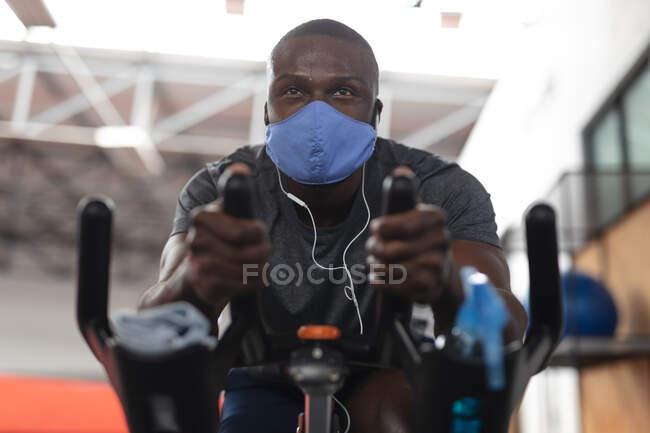 Fit Man Afroamerikaner mit Mundschutz und Kopfhörer beim Training auf dem Fahrrad im Fitnessstudio. Soziale Distanzierung von Quarantäne während der Coronavirus-Pandemie — Stockfoto