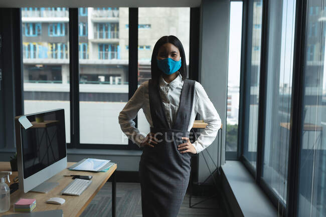 Porträt einer asiatischen Frau mit Gesichtsmaske, die mit den Händen auf den Hüften im modernen Büro steht. Soziale Distanzierung von Quarantäne während der Coronavirus-Pandemie — Stockfoto