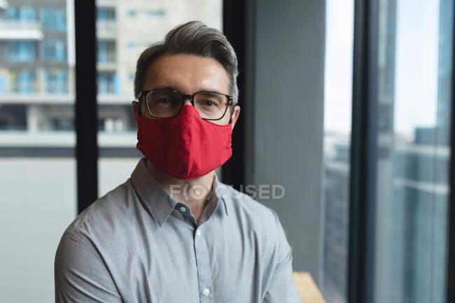 Porträt eines kaukasischen Mannes mit Mundschutz im modernen Büro. Soziale Distanzierung von Quarantäne während der Coronavirus-Pandemie — Stockfoto
