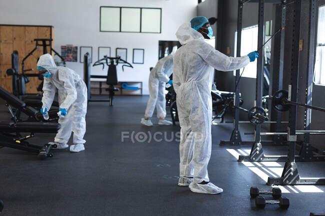 Equipe de trabalhadores vestindo roupas protetoras e máscaras faciais limpando o ginásio usando desinfetante. bloqueio de quarentena por distanciamento social durante a pandemia do coronavírus — Fotografia de Stock