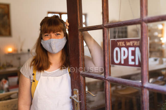 Портрет жінки, яка носить маску обличчя на гончарній майстерні. маленьке творче підприємство під час 19-ї коронавірусної пандемії. — стокове фото