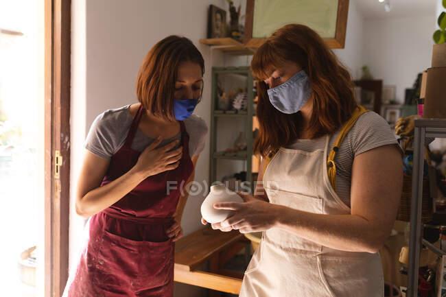 Duas oleiros caucasianas em máscaras faciais a trabalhar no estúdio de cerâmica. a usar avental, a olhar para um prato de barro. pequeno negócio criativo durante a pandemia do coronavírus covid 19. — Fotografia de Stock