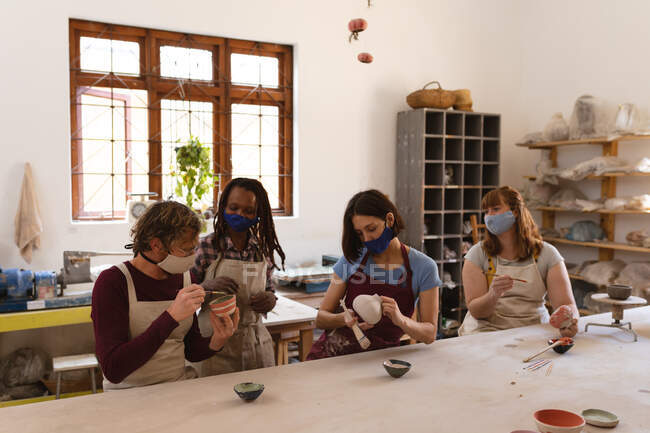 Multi-ethnic group of potters in face masks working in pottery studio. wearing aprons, painting plates. small creative business during covid 19 coronavirus pandemic. — Stock Photo