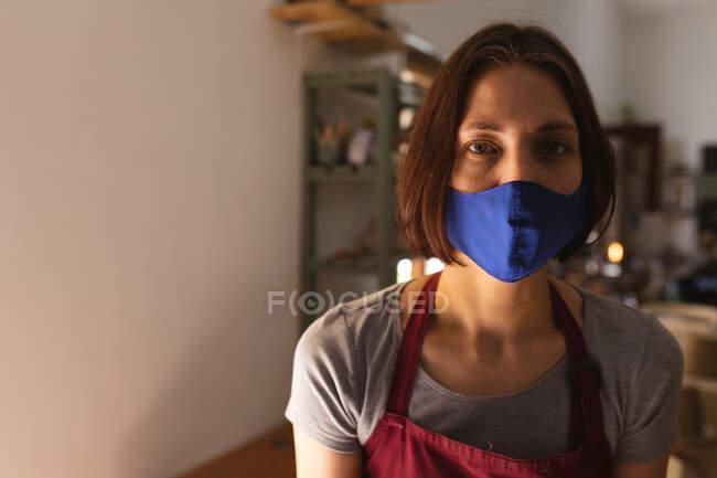 Porträt einer kaukasischen Frau mit Gesichtsmaske im Töpferatelier. kleine kreative Unternehmen während covid 19 Coronavirus-Pandemie. — Stockfoto