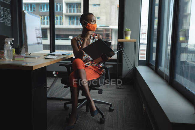 African american woman wearing face mask working in office. sitting at desk reading documents. hygiene and social distancing in the workplace during coronavirus covid 19 pandemic. — Stock Photo