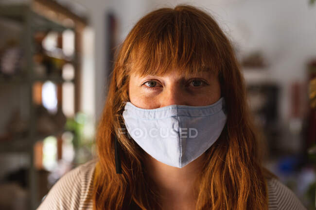Portrait de femme caucasienne portant un masque facial au studio de poterie. petite entreprise créative pendant la pandémie de coronavirus covid 19. — Photo de stock
