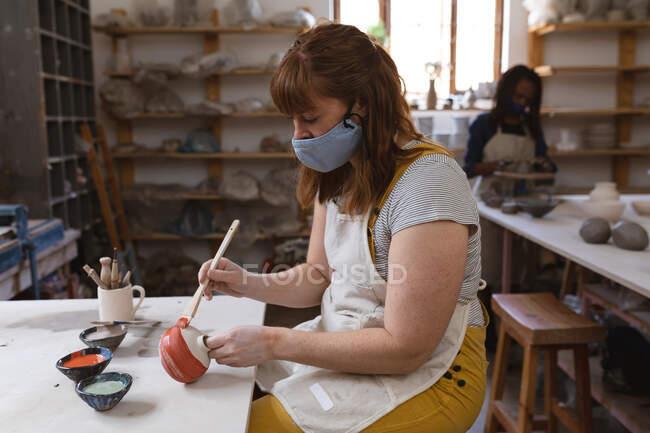 Oleiro feminino caucasiano em máscara facial trabalhando no estúdio de cerâmica. a usar avental, a trabalhar numa mesa de trabalho, a pintar um prato. pequeno negócio criativo durante a pandemia do coronavírus covid 19. — Fotografia de Stock