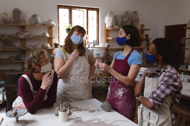 Multi-ethnische Gruppe von Töpfern mit Mundschutz, die im Töpferatelier arbeiten. Schürzen tragen, reden. kleine kreative Unternehmen während covid 19 Coronavirus-Pandemie. — Stockfoto