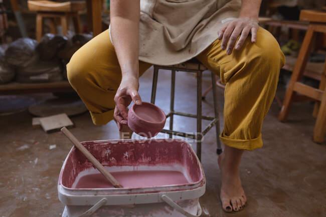 Töpferin arbeitet im Töpferatelier. Malerei einer Schale. kleine kreative Unternehmen während covid 19 Coronavirus-Pandemie. — Stockfoto