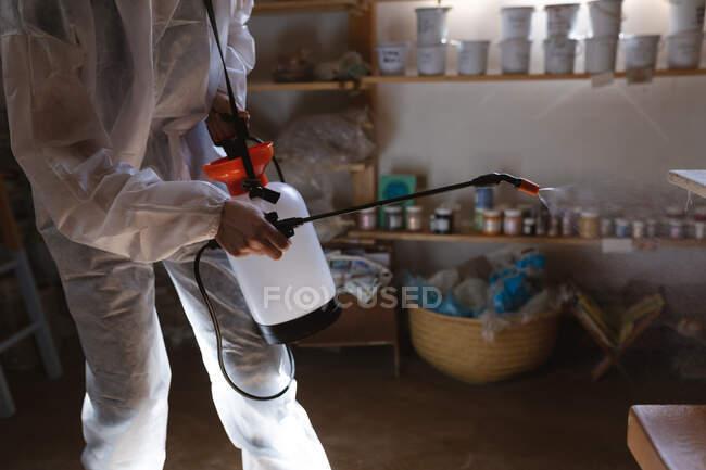 Limpador masculino caucasiano em roupas protetoras que trabalham no estúdio de cerâmica. a desinfectar o local todo. pequeno negócio criativo durante a pandemia do coronavírus covid 19. — Fotografia de Stock
