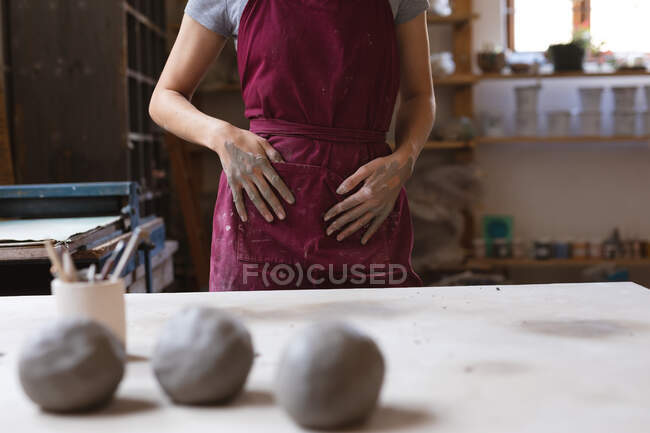 Female potter working in pottery studio. wiping her hands in an apron. small creative business during covid 19 coronavirus pandemic. — Stock Photo