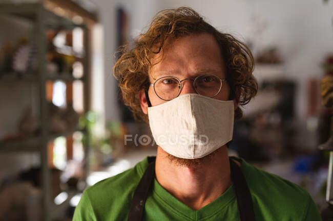 Ritratto di uomo caucasico mascherato allo studio di ceramica. piccola attività creativa durante covid 19 coronavirus pandemia. — Foto stock