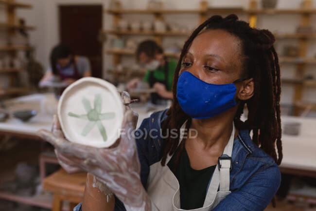 Töpferin mit Gesichtsmaske, die im Töpferatelier arbeitet. Schürze tragen, an einem Arbeitstisch arbeiten, einen Teller bemalen. kleine kreative Unternehmen während covid 19 Coronavirus-Pandemie. — Stockfoto