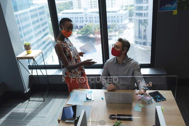 Diversi colleghi uomini e donne che indossano maschere facciali parlano tra loro in un ufficio moderno. isolamento di quarantena a distanza sociale durante la pandemia di coronavirus — Foto stock