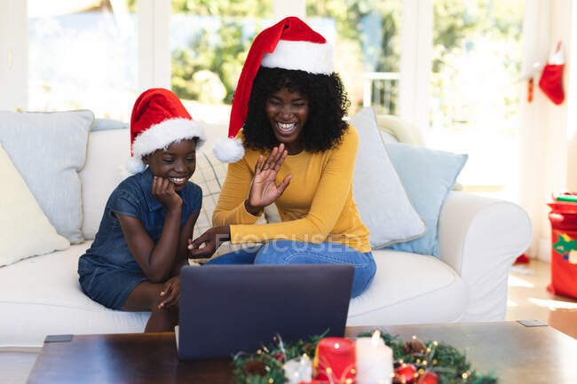 African american mother and daughter having video chat on laptop wearing santa hats during christmas at home. social distancing during covid 19 coronavirus quarantine lockdown. — Stock Photo