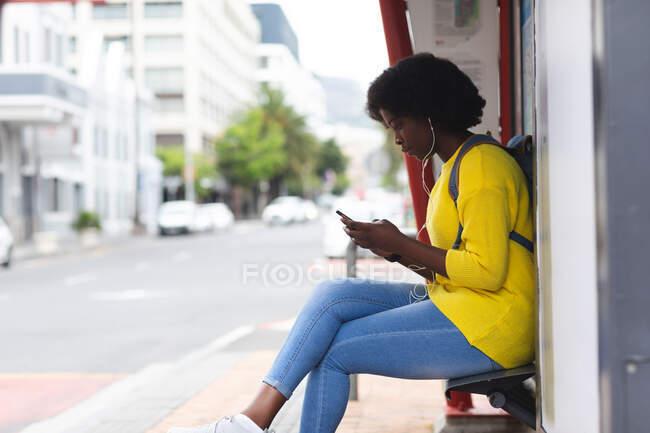Африканська американка користується смартфоном на вулиці. сидячи на лавці і слухаючи музику з навушниками. і десь у місті під час коронавірусної пандемії.. — стокове фото