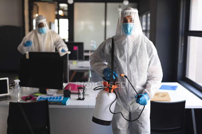 Porträt eines männlichen Gesundheitshelfers im modernen Büro. Sie tragen Mundschutz und Schutzkleidung mit Desinfektionsspray. Reinigung und Desinfektion Prävention und Kontrolle von Covid-19-Epidem — Stockfoto
