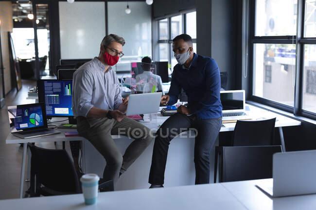 Різні чоловіки-колеги в масках на обличчі, використовуючи ноутбук, сидять за столом у сучасному офісі. Відстань до карантину під час пандемії коронавірусу — стокове фото