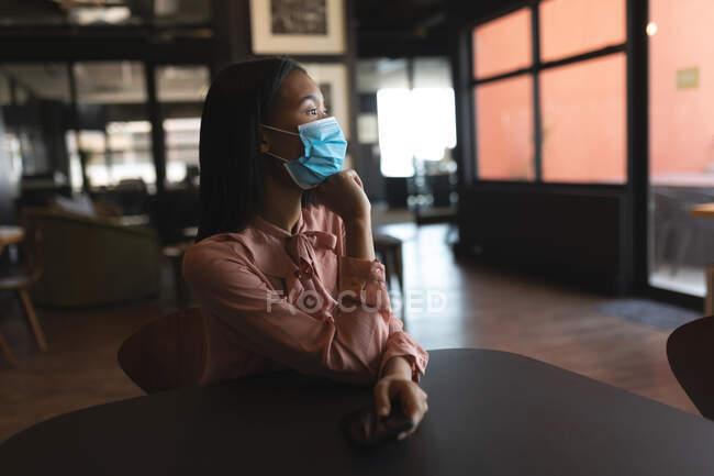 Asiatin mit Gesichtsmaske sitzt im modernen Büro. Soziale Distanzierung von Quarantäne während der Coronavirus-Pandemie — Stockfoto