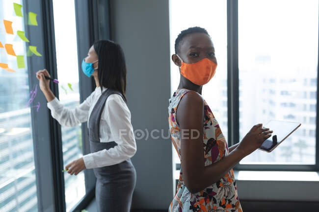 Portrait of african american woman wearing face mask using digital tablet at modern office. social distancing quarantine lockdown — Stock Photo