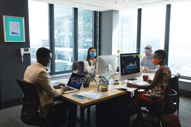 Различные коллеги в офисных масках, работающие за компьютерами, сидящими за их столами. гигиена и социальное дистанцирование на рабочем месте во время пандемии коронавируса 19. — стоковое фото