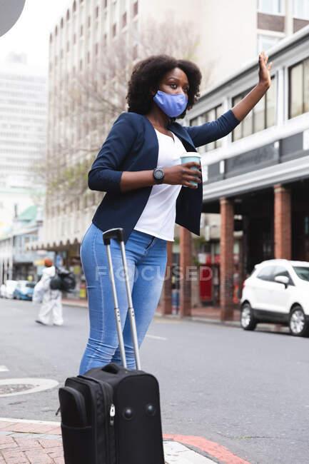 Африканская американка в маске на улице держит чашку кофе и поднимает руку. в городе во время 19 пандемических коронавирусов. — стоковое фото
