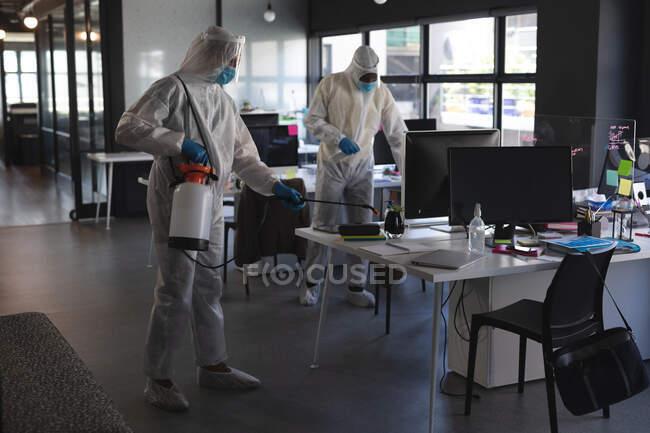 Squadra di operatori sanitari che indossano indumenti protettivi ufficio di pulizia utilizzando disinfettante. pulizia e disinfezione prevenzione e controllo dell'epidemia di covid-19 — Foto stock