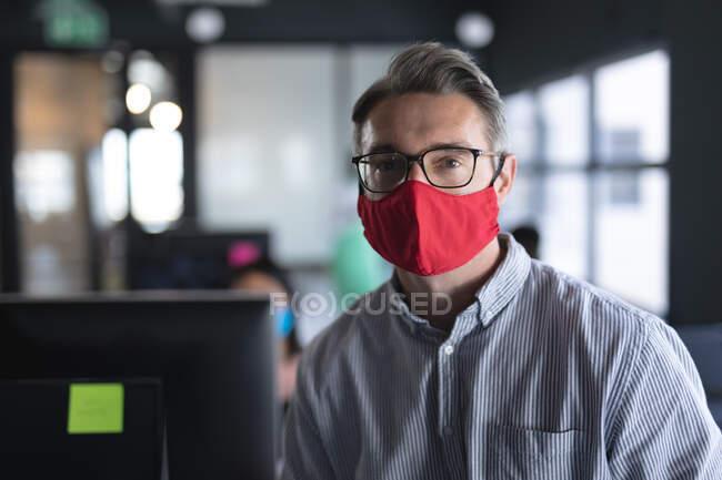 Porträt eines kaukasischen Mannes mit Gesichtsmaske, während er auf seinem Schreibtisch im modernen Büro sitzt. Hygiene und soziale Distanzierung am Arbeitsplatz während der Coronavirus-Pandemie 19. — Stockfoto