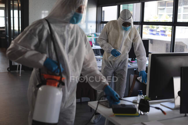 Team of health workers wearing protective clothes cleaning office using disinfectant. cleaning and disinfection infection prevention and control of covid-19 epidemic — Stock Photo