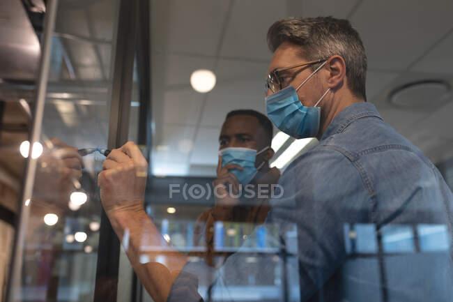 Kaukasischer Mann mit Gesichtsmaske und Filzstift auf Glasplatte im modernen Büro. Soziale Distanzierung von Quarantäne während der Coronavirus-Pandemie — Stockfoto