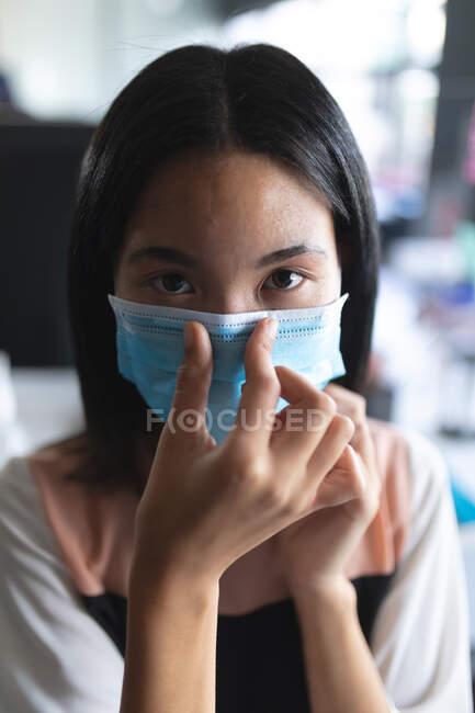 Ritratto di donna asiatica con maschera facciale che si tocca il naso nell'ufficio moderno. isolamento di quarantena a distanza sociale durante la pandemia di coronavirus — Foto stock