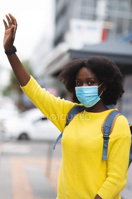 Portrait de femme afro-américaine portant un masque dans la rue, levant la main. dehors et autour dans la ville pendant la pandémie de coronavirus covid 19. — Photo de stock