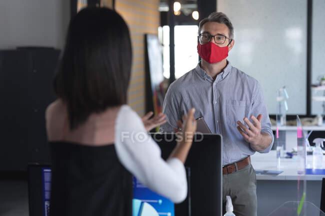 Homem e mulher caucasianos usando máscaras faciais conversando um com o outro no escritório moderno. bloqueio de quarentena por distanciamento social durante a pandemia do coronavírus — Fotografia de Stock