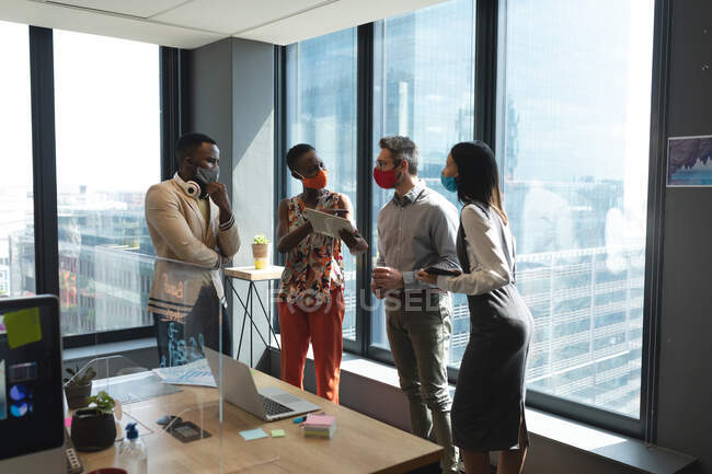 Diversi colleghi che indossano maschere facciali discutono insieme al moderno ufficio isolamento sociale distanza quarantena durante la pandemia coronavirica — Foto stock