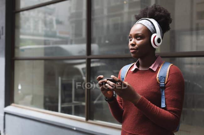 Portrait de femme afro-américaine utilisant un smartphone dans la rue, écoutant de la musique avec écouteurs allumés. dehors et autour dans la ville pendant la pandémie de coronavirus covid 19. — Photo de stock