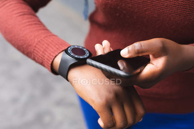 Portrait of african american woman using smartphone and smartwatch on street out and about in the city during covid 19 coronavirus pandemic. — Stock Photo